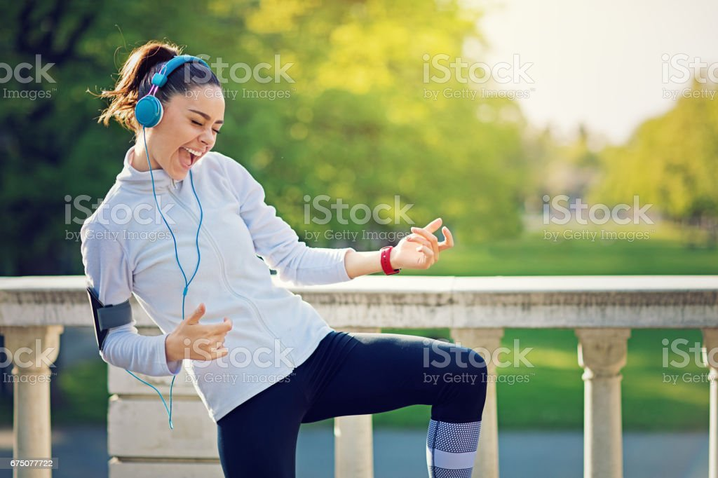 Runner girl is pretend playing guitar at her favorite song stock photo