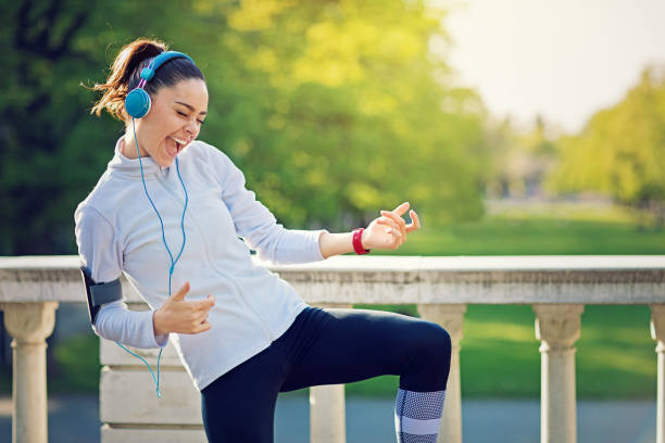 runner girl is pretend playing guitar at her favorite song - music stock photos and pictures