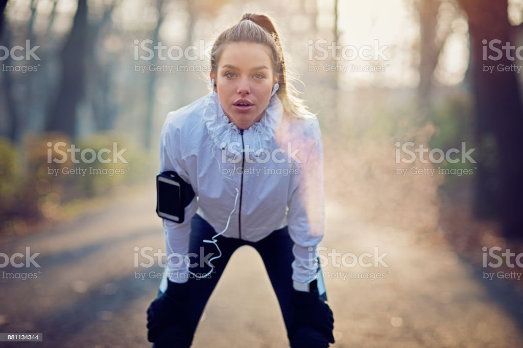 Runner girl is resting exhausted in the foggy morning stock photo