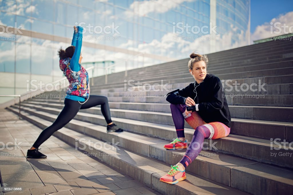 Runner girl is resting on the city stairs and checking her smart watch stock photo