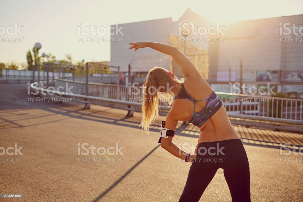 A runner girl makes a warm-up before jogging in the autumn. stock photo