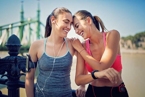 läufer-mädchen sind entlang des flusses ausruhen und spaß gemeinsam zu machen - motivationsmusik stock-fotos und bilder