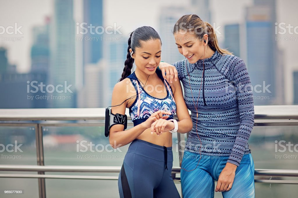 Runner girls are resting and watching a smart watch after run zbiór zdjęć royalty-free