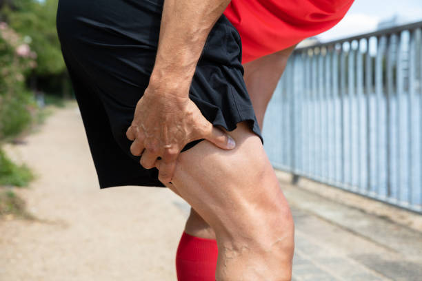 Runner Holding His Injured Leg Close-up Of A Male Runner Holding His Injured Leg hamstring stock pictures, royalty-free photos & images