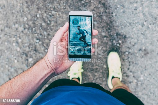 istock Runner holds smart phone with app during run 621838288