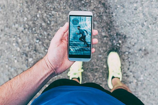 Runner holds smart phone with app during run - foto de acervo