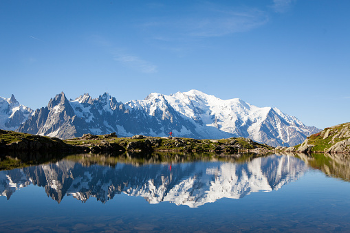 Runner in red runs in the French Alps near Chamonix with the Mont Blanc in the background.