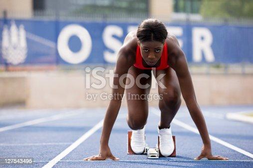 istock Runner in start block on track 127543495