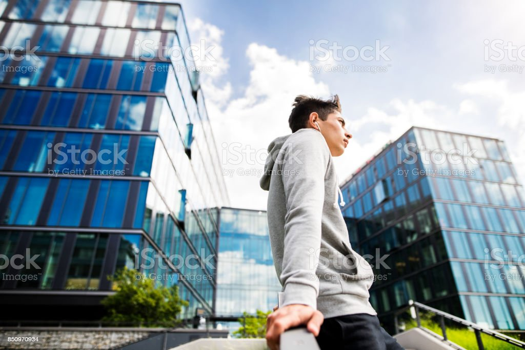 Runner in the city resting in front of glass buildings. stock photo