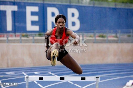 istock Runner jumping over hurdles on track 127543492