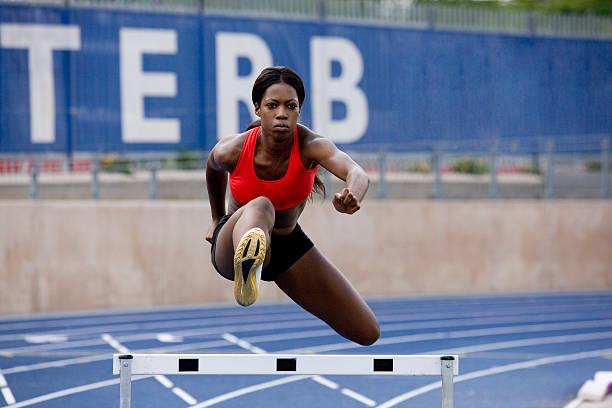 läufer springen über hürden auf track - konzentrationsübungen stock-fotos und bilder