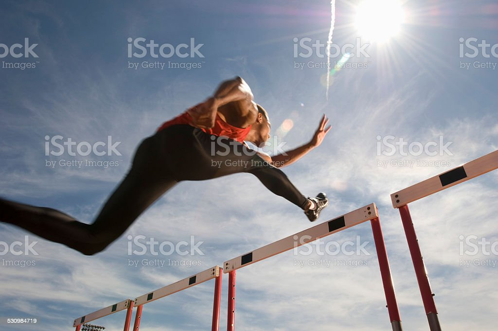 Runner jumping over running hurdle stock photo