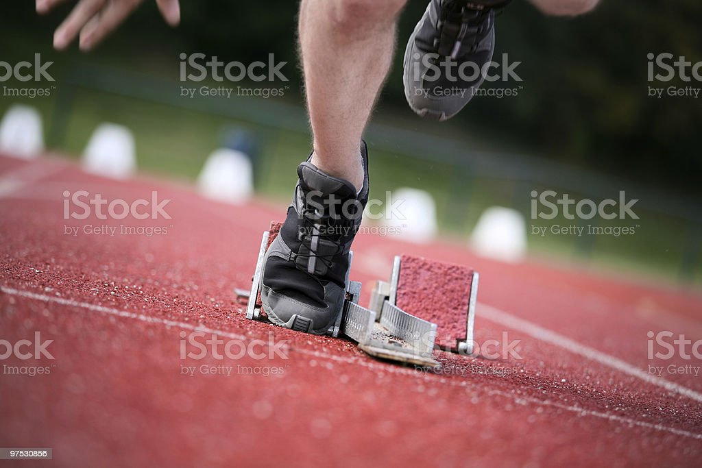 Runner leaving the starter blocks on a track. royalty-free stock photo