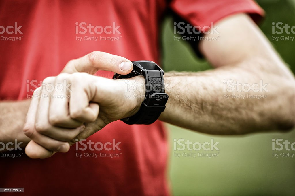 Runner looking at sports watch stock photo