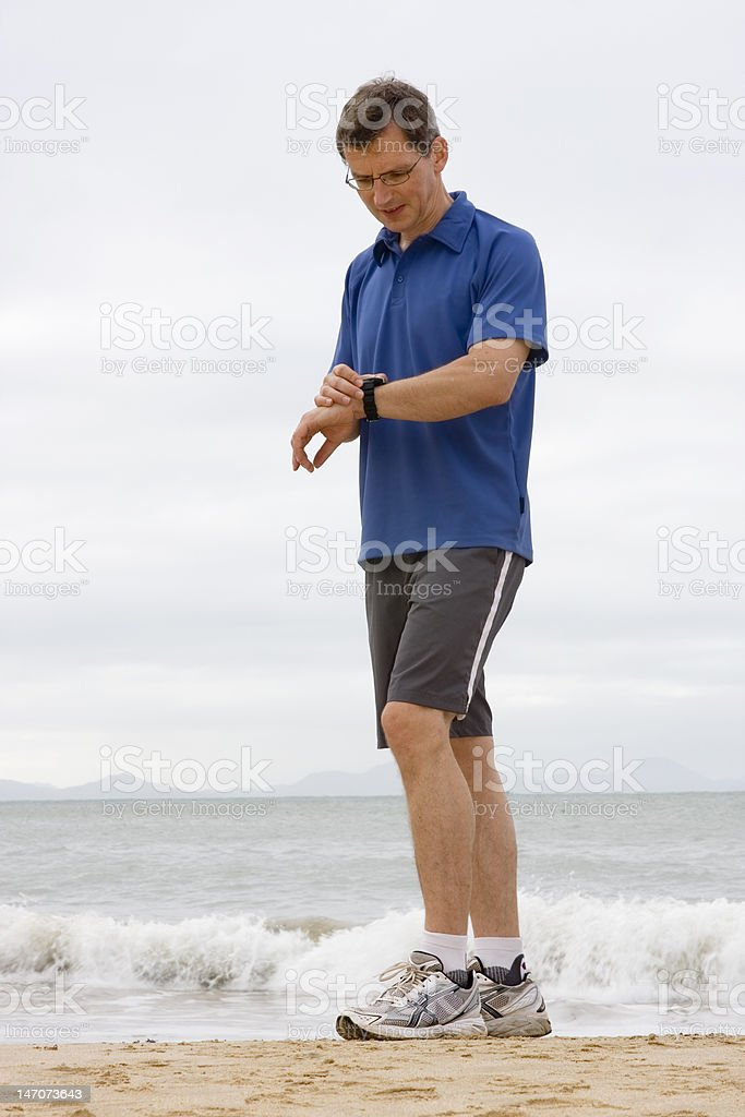 Runner looking at stop watch royalty-free stock photo
