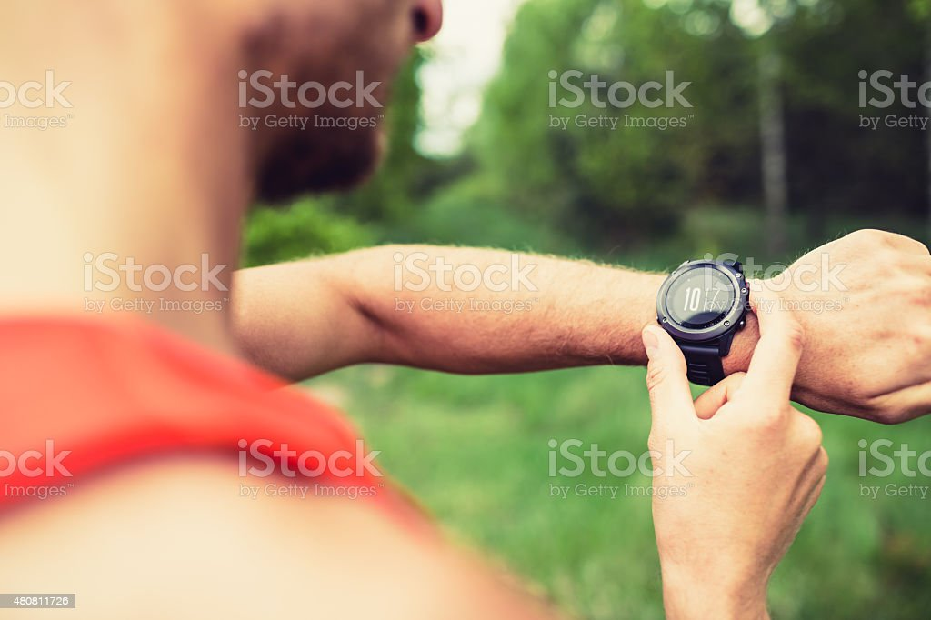 Runner looking checking sport watch stock photo