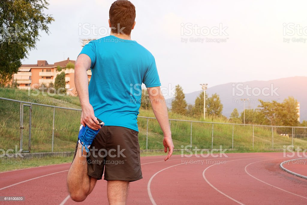 Runner making stretching on the track stock photo