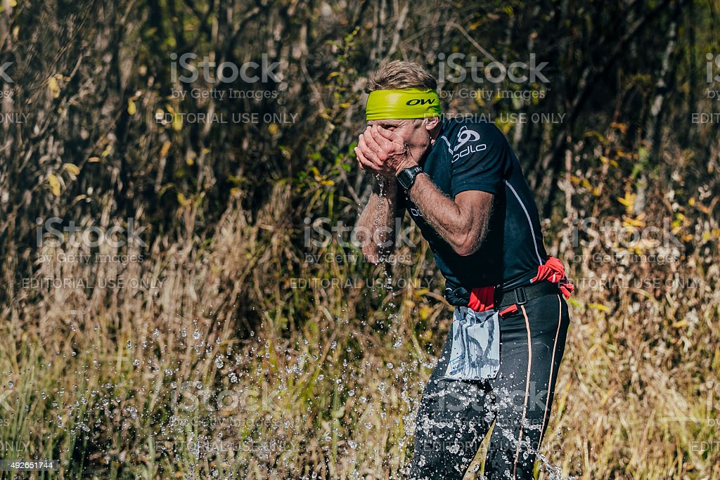 runner man drinks water from a mountain stream stock photo