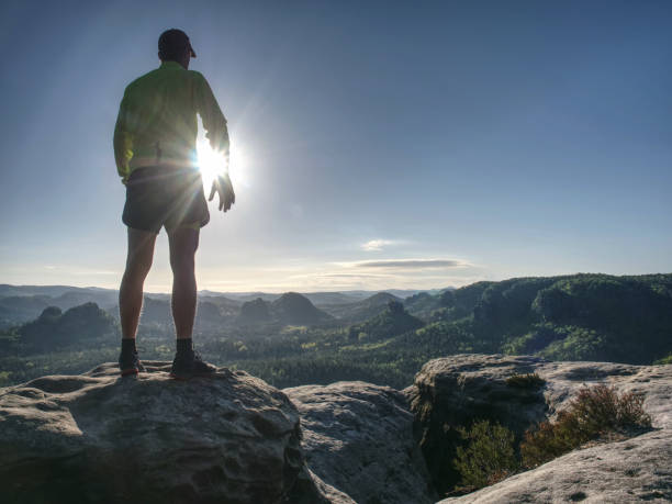 Runner man on rocky road of mountain nature. Male sprinter stock photo