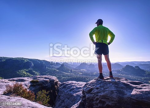 Successful runner man raising body on the cliff with the golden green jersey, sunny blue sky in  background