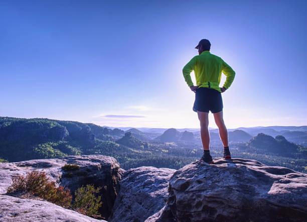 Runner man raising body on the cliff with the green jersey stock photo