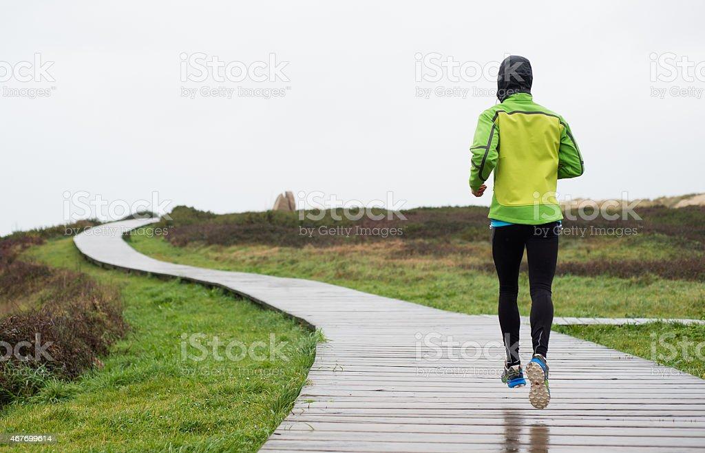 Runner man running in a rainy day stock photo