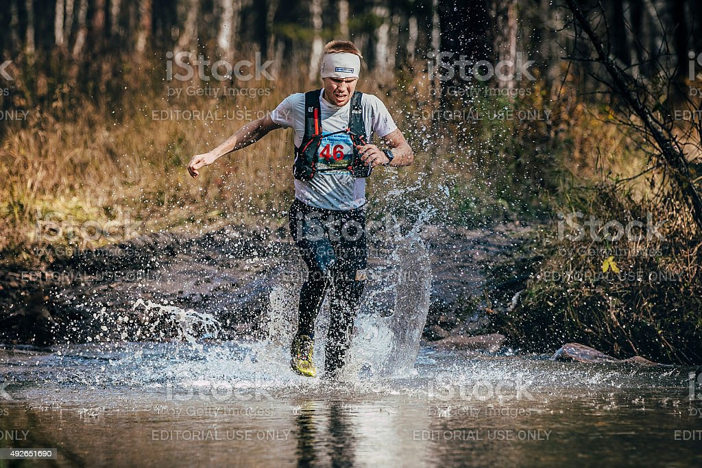 runner middle-aged man crossing a mountain river stock photo
