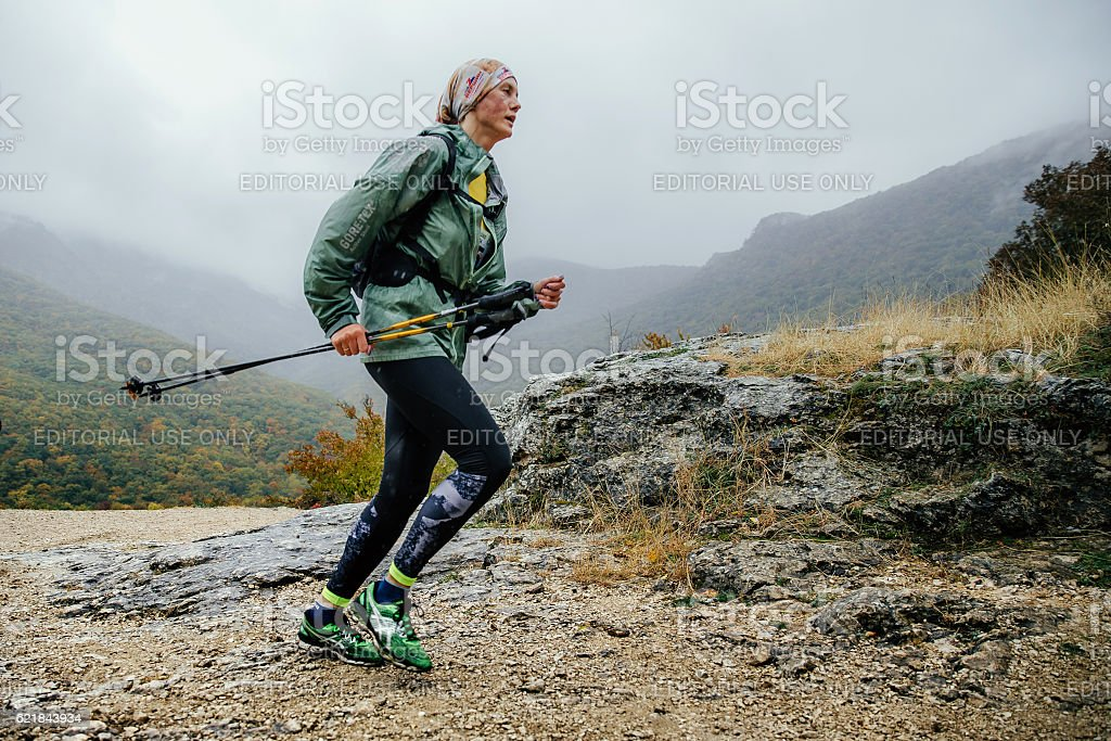 runner middle-aged woman running in rain on a mountain trail stock photo