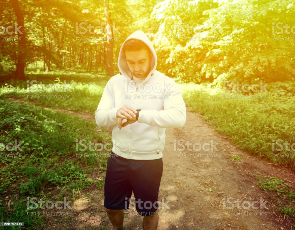 Runner on mountain trail looking at sports smart watch stock photo