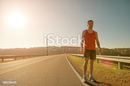 Runner standing on the side of road contemplating.