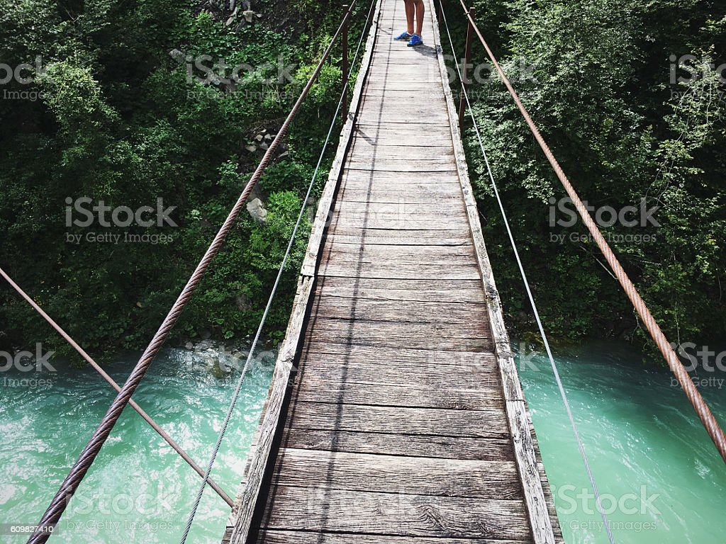Runner on the wooden bridge over the mountain river stock photo