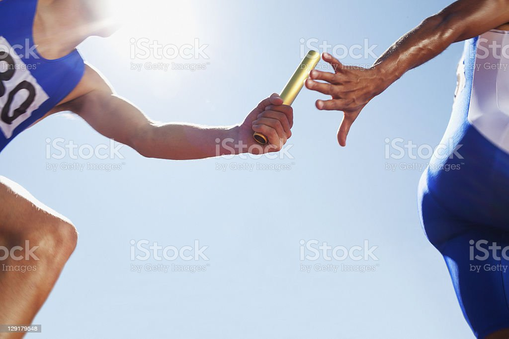 Runner passing baton during relay event stock photo