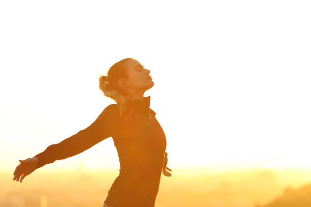 Runner resting breathing fresh air at sunset Profile of a runner resting breathing deeply fresh air outstretching arms at sunset wellbeing stock pictures, royalty-free photos & images