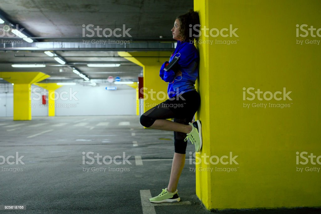 Runner resting on a parking lot stock photo