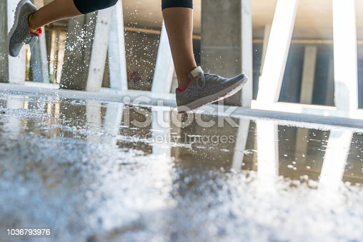 494003079istockphoto Runner running through puddle 1036793976