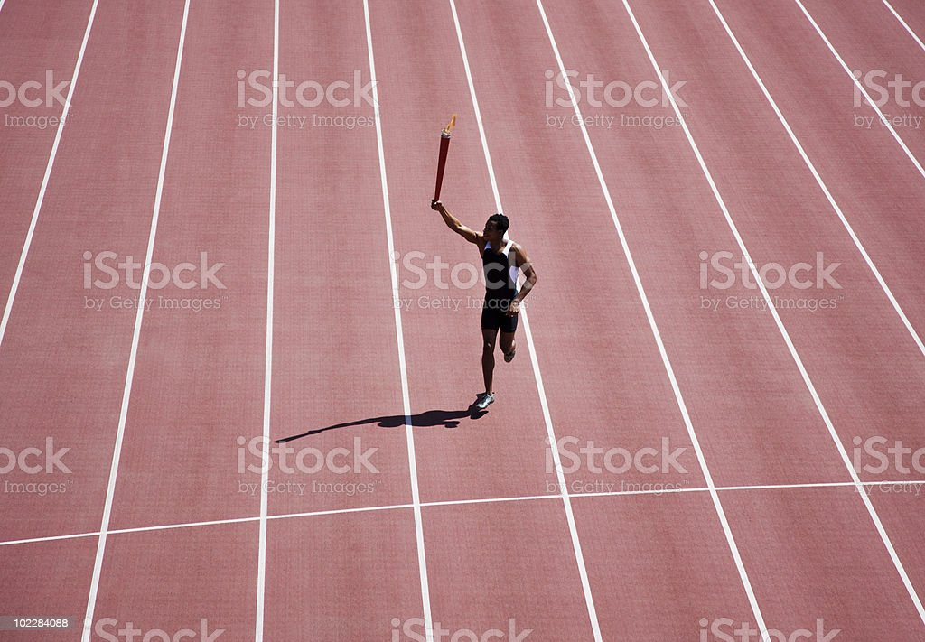 Runner running with torch on track stock photo