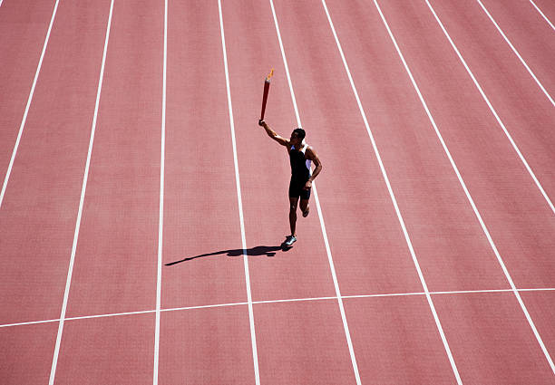 Runner running with torch on track  flaming torch stock pictures, royalty-free photos & images