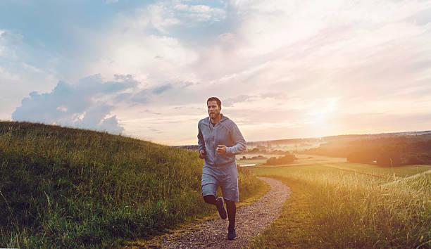 runner runs outside on small road at sunset - trail running fotografías e imágenes de stock