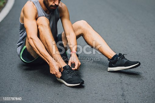Runner Sitting on the Road and Tying Shoelaces on Sneakers