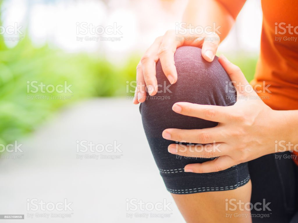 Runner sport knee injury. Woman in pain while running in the garden. royalty-free stock photo