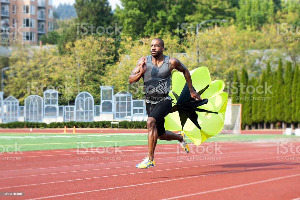Runner Sprinting Down Track with Parachute stock photo