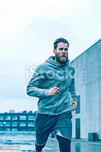 Male runner wears hooded shirt and sprints. The sky is grey.