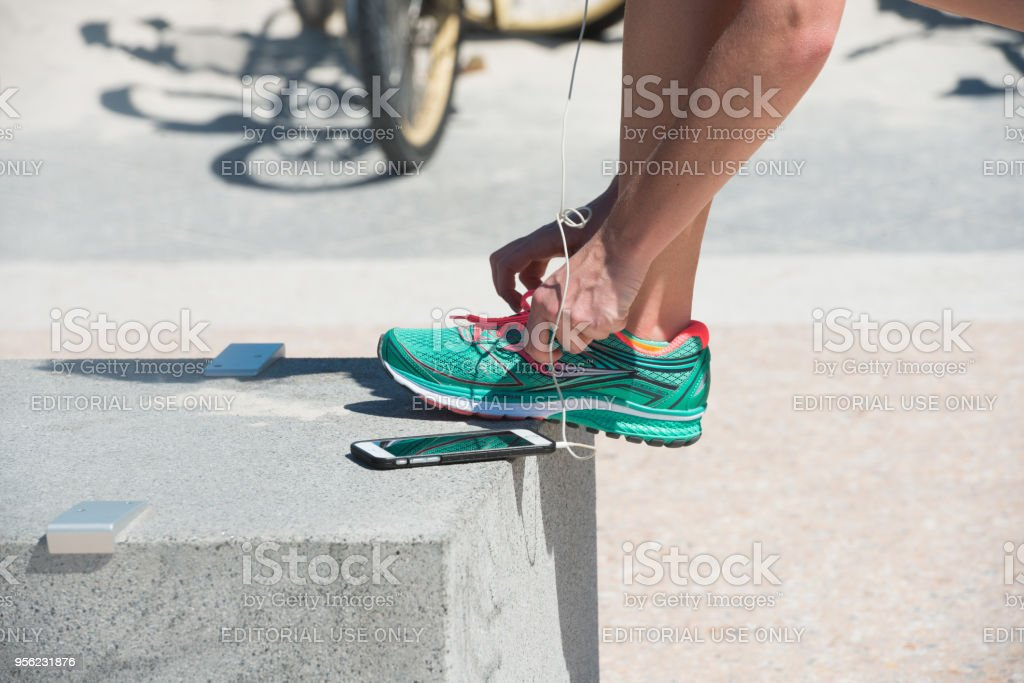 Runner Stops to Tie Sneaker Shoe Laces stock photo
