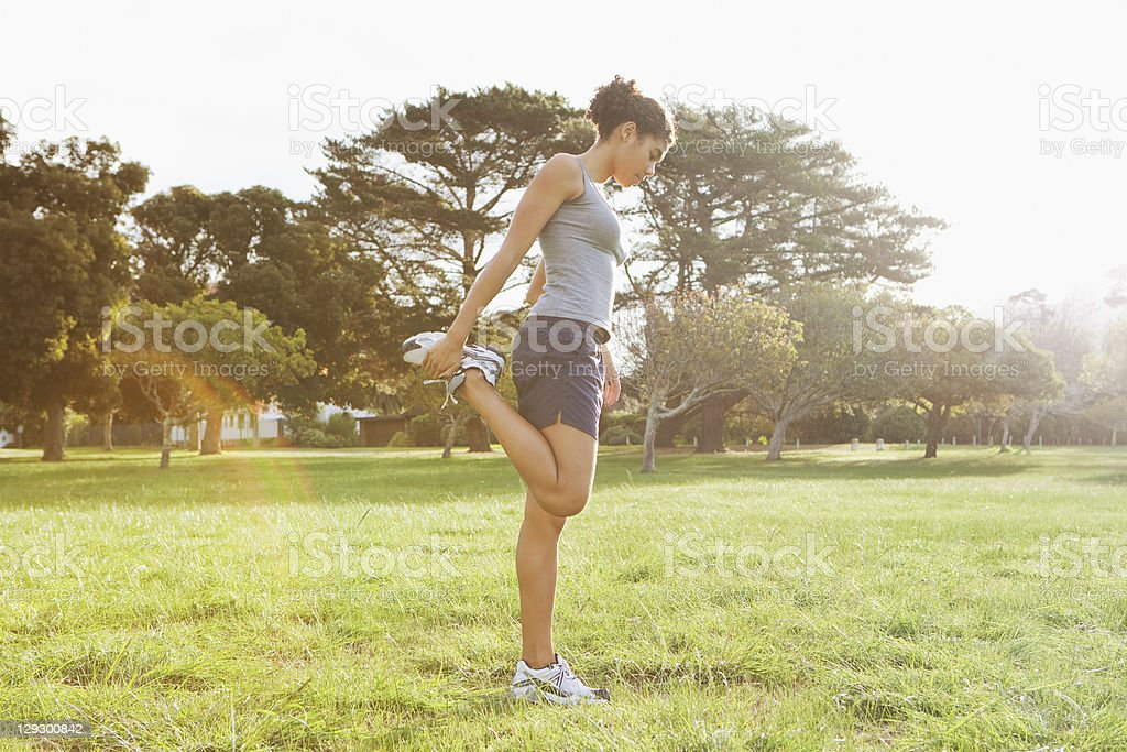 Runner stretching in field stock photo