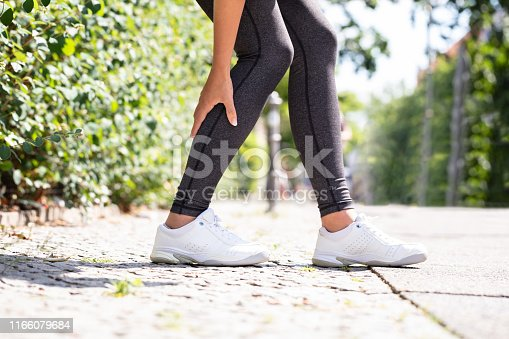 Close-up Of A Female Runner Suffering From Pain In Calf Muscle