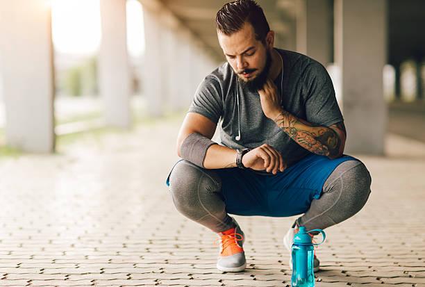 läufer pulsmessung. - laufende tattoos stock-fotos und bilder