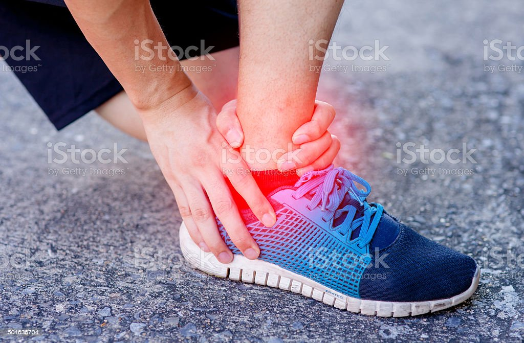 Runner touching painful twisted or broken ankle. Runner training accident - Royalty-free Adult Stock Photo