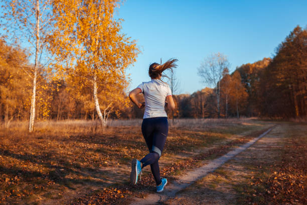 Runner training and exercising in autumn park. Woman running at sunset. Active healthy lifestyle