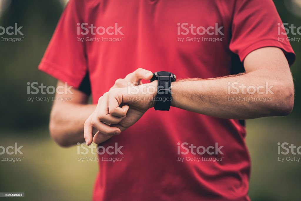 Runner training and using stopwatch with heart rate monitor stock photo