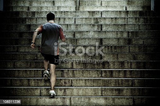 Athlete training on steep old worn concrete stairs - toned image for dramatic feel.